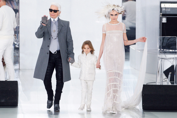 German fashion designer Karl Lagerfeld (L) acknowledges the public along with his godson Hudson Kroenig and British model Cara Delevingne during the Chanel Haute Couture Spring-Summer 2014 collection show, on January 21, 2014 at the Grand Palais in Paris. AFP PHOTO / PATRICK KOVARIK (Photo credit should read PATRICK KOVARIK/AFP/Getty Images)
